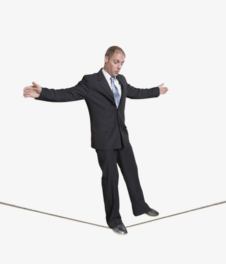 Businessman walking on a tightrope : Stock Photo