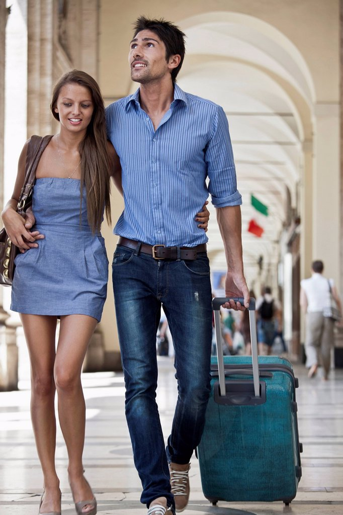Stock Photo: 1589R-172138 Caucasian couple pulling luggage in city