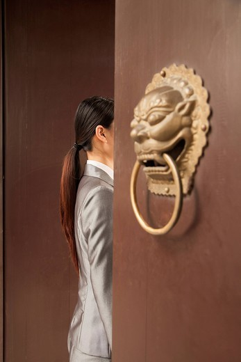 Chinese businesswoman standing in doorway : Stock Photo