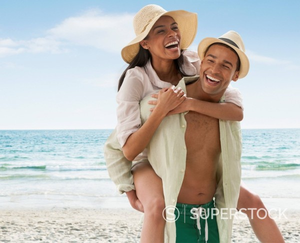 Stock Photo: 1589R-173028 Smiling man carrying girlfriend on beach