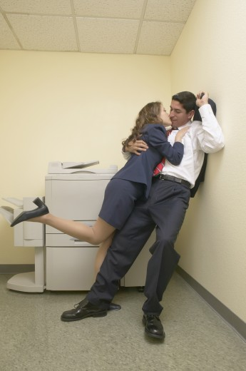 Stock Photo: 1589R-17488 Businesspeople kissing by copy machine