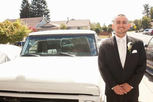 Hispanic groom standing next to truck : Stock Photo