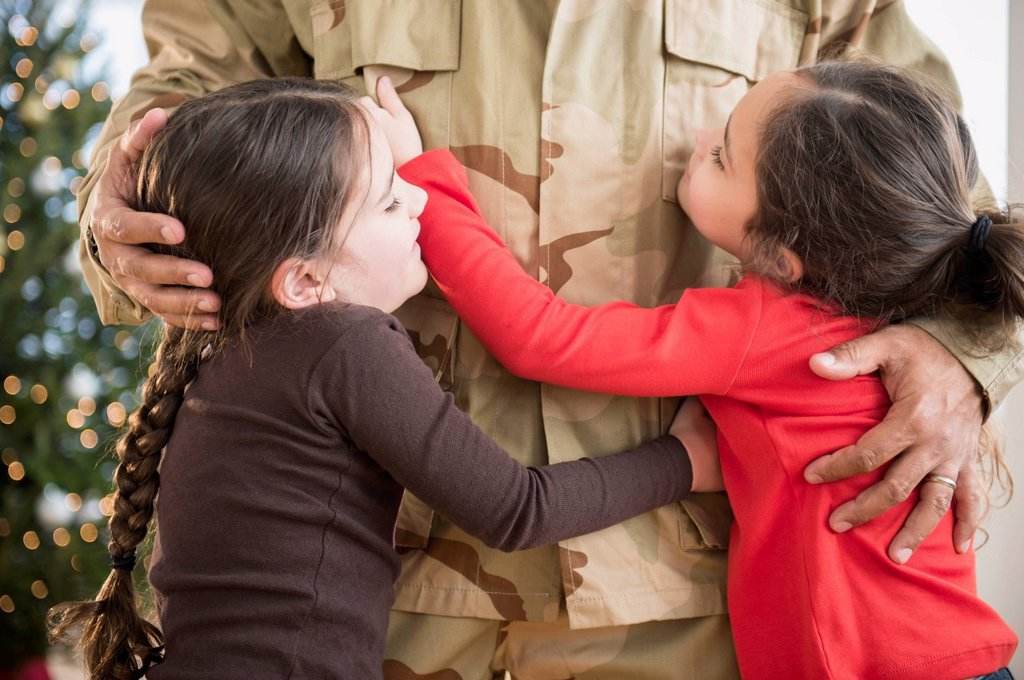 Daughters hugging soldier father : Stock Photo