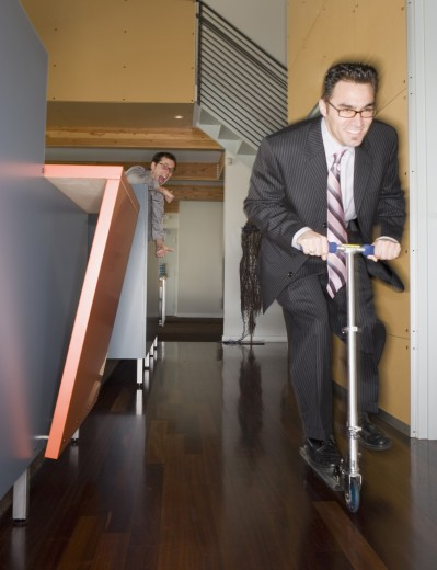 Businessman riding a scooter in office area : Stock Photo