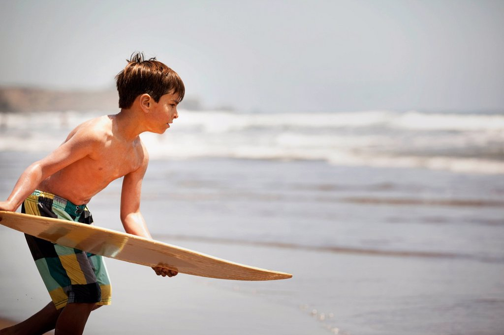 Stock Photo: 1589R-175888 Mixed race boy holding board on beach