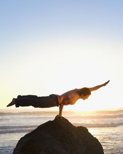 Man balancing on one arm : Stock Photo