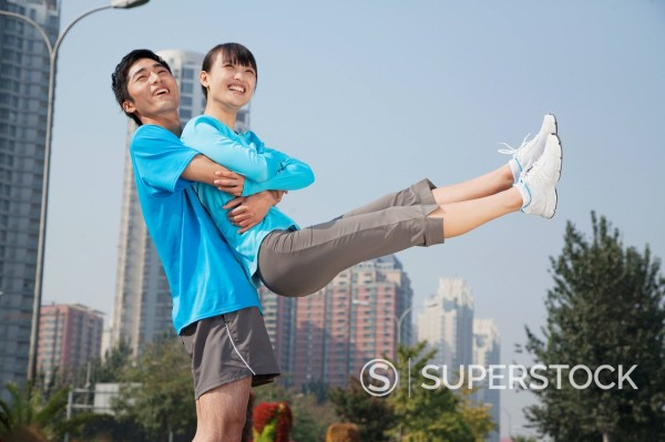 Chinese man lifting girlfriend in city : Stock Photo