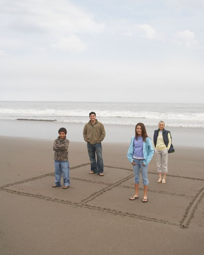 Stock Photo: 1589R-17843 Portrait of family standing in boxes drawn in sand at beach