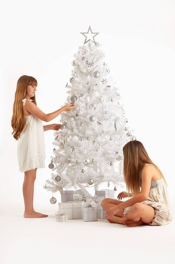 Caucasian girls decorating Christmas tree : Stock Photo