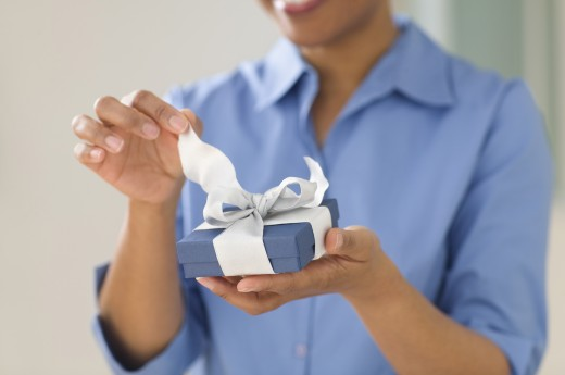 Close up of womanís hands opening gift : Stock Photo
