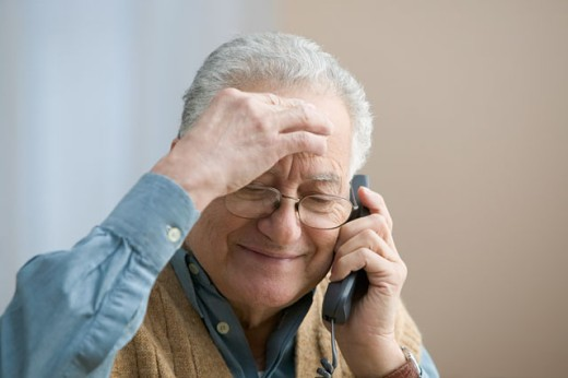Stock Photo: 1589R-18035 Older man rubbing his forehead as he talks on the telephone
