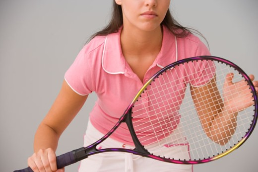 Mid section of teenage girl holding tennis racket : Stock Photo