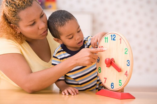 Stock Photo: 1589R-18771 Mother teaching son to tell time