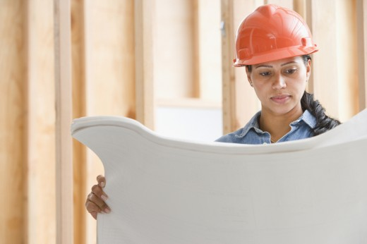 Female construction worker reading plans : Stock Photo