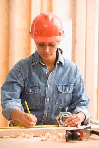 Stock Photo: 1589R-18800 Female construction worker measuring wood with tape measure