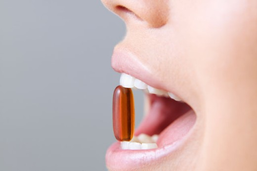 Young woman holding a pill between her teeth : Stock Photo