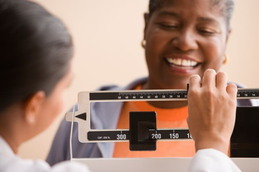 Doctor weighing woman : Stock Photo