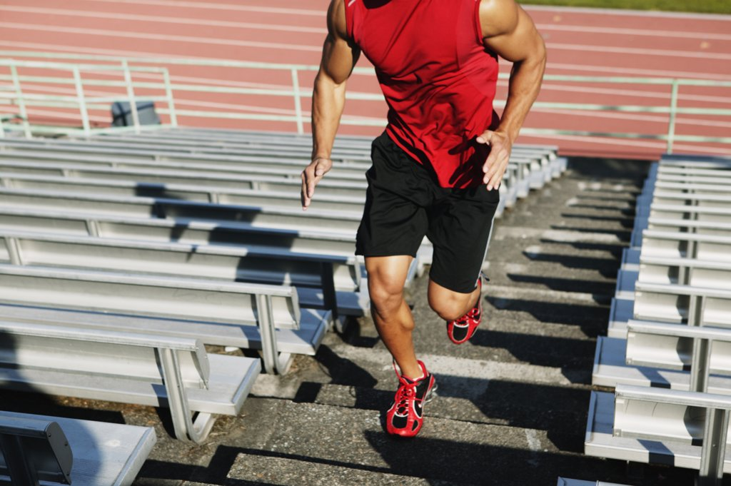 Male athlete running up steps : Stock Photo