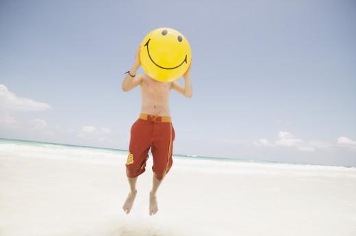 Stock Photo: 1589R-21335 Young boy holding a smiley face beach ball over his face
