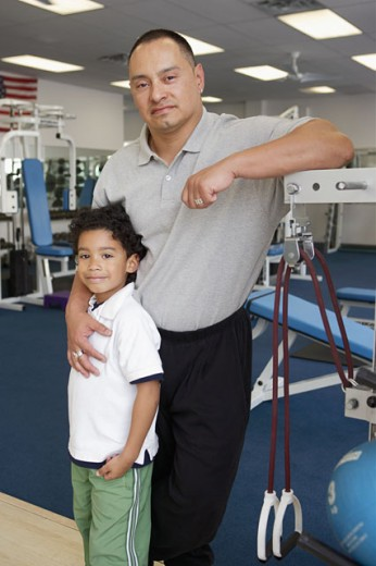 Physical trainer posing for the camera with his son in a gym : Stock Photo