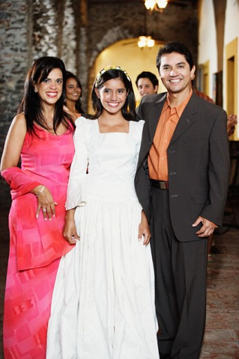 Family in evening wear smiling for the camera : Stock Photo