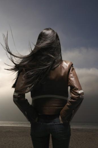 Woman standing on windy beach : Stock Photo