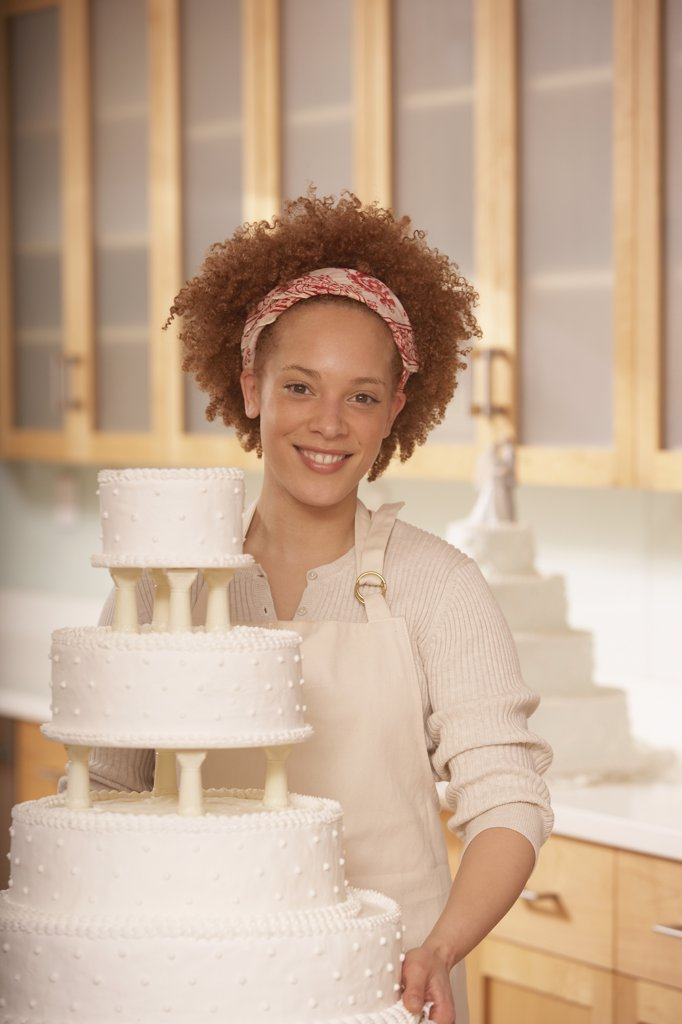 Stock Photo: 1589R-23018 African female baker next to a wedding cake, Richmond, Virginia, United States