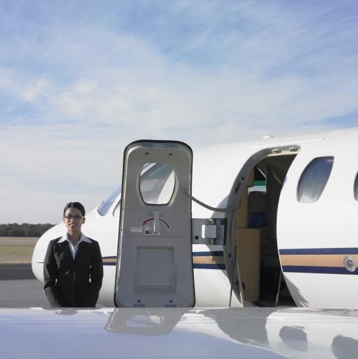Stock Photo: 1589R-23130 Female flight attendant next to airplane door, Perth, Australia