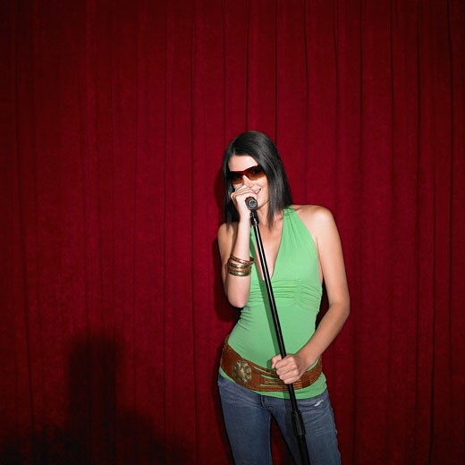 Stock Photo: 1589R-23180 Young woman singing into microphone, Perth, Australia