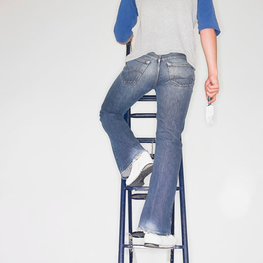 Man climbing a ladder with paintbrush : Stock Photo