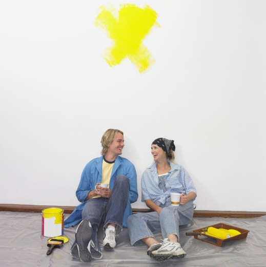 Stock Photo: 1589R-23242 Couple having coffee on tarp with paint and paintbrushes
