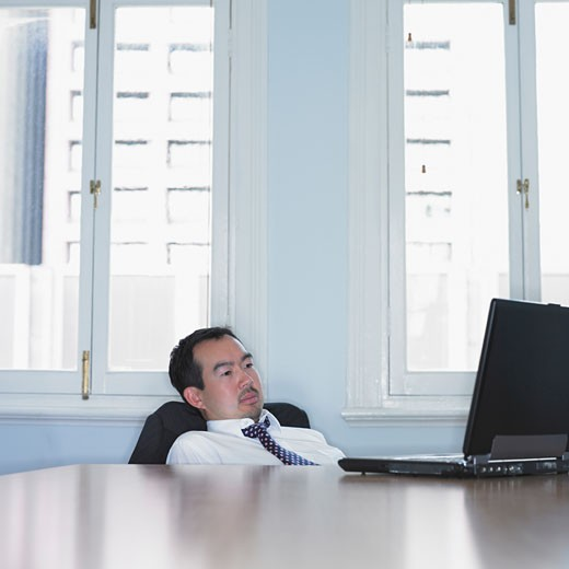 Asian businessman slouched down in his chair : Stock Photo