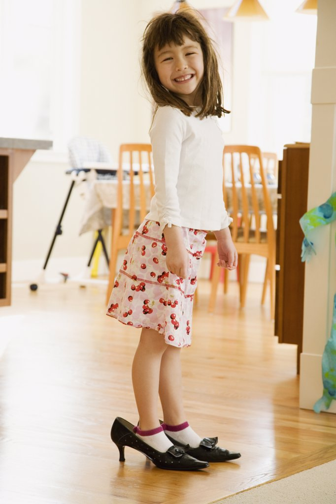 Young girl wearing mother's shoes : Stock Photo