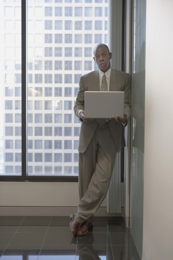 Stock Photo: 1589R-23473 African businessman standing next to window with laptop, Los Angeles, California, United States