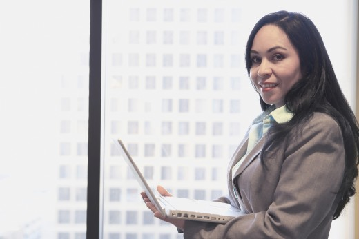 Hispanic businesswoman with laptop next to window, Los Angeles, California, United States : Stock Photo