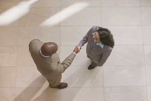 High angle view of businessman and businesswoman shaking hands : Stock Photo