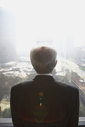 Stock Photo: 1589R-23505 Senior businessman looking out window, Los Angeles, California, United States