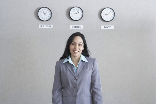 Hispanic businesswoman standing under world time zone clocks : Stock Photo