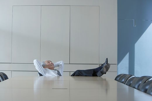 Senior Asian businessman sitting at head of conference table with his feet up : Stock Photo