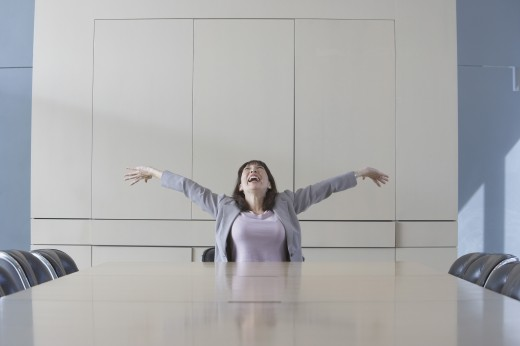Stock Photo: 1589R-23544 Businesswoman sitting at head of conference table stretching