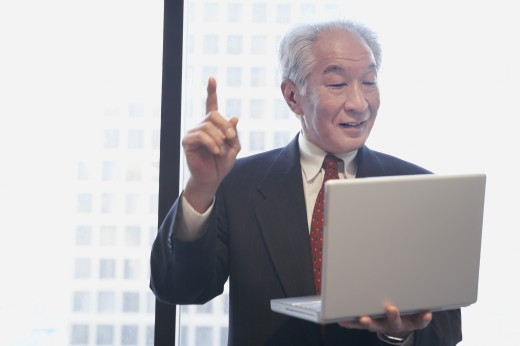Stock Photo: 1589R-23549 Senior Asian businessman holding laptop and pointing his index finger up