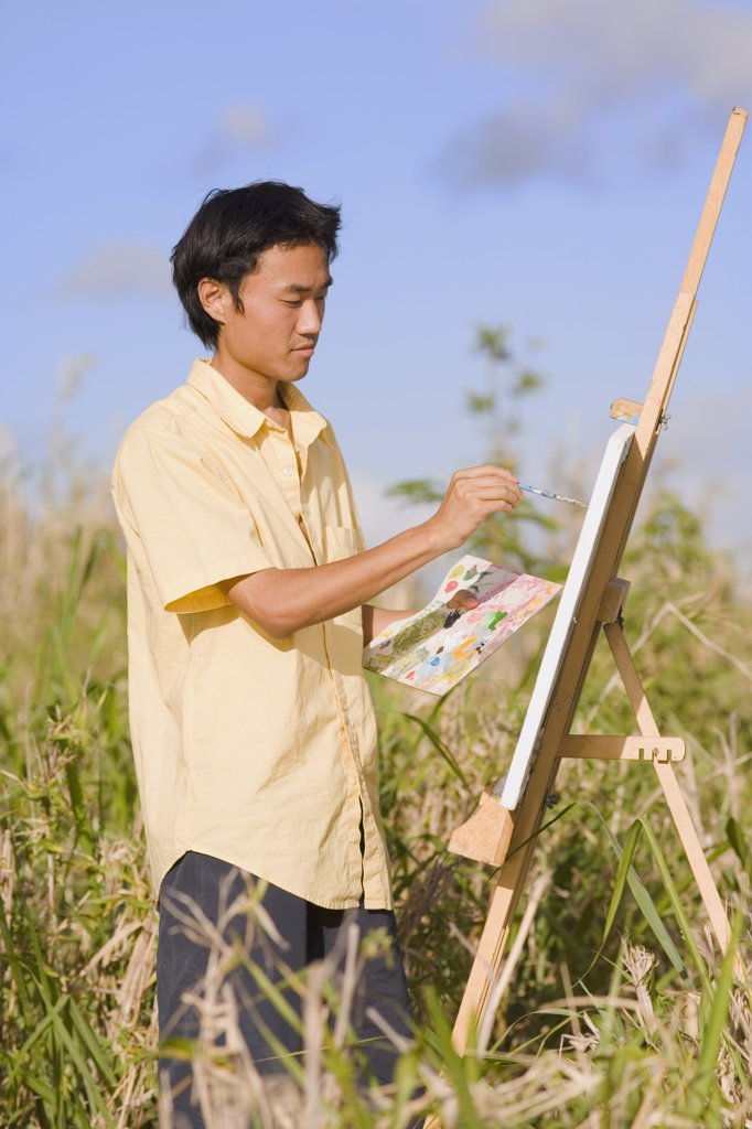 Stock Photo: 1589R-23572 Asian man painting at easel outdoors, Florianopolis, Brazil