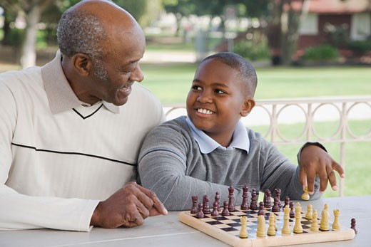 African American boy playing chess with grandfather : Stock Photo