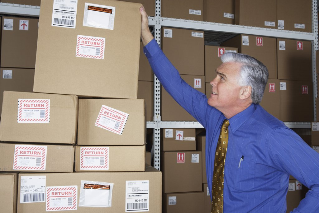 Stock Photo: 1589R-23768 Businessman in warehouse looking at returned packages