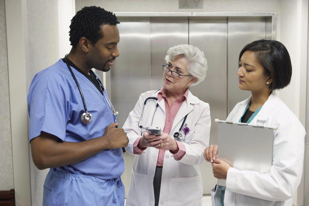 Hospital staff talking in front of elevator, Bethesda, Maryland, United States : Stock Photo