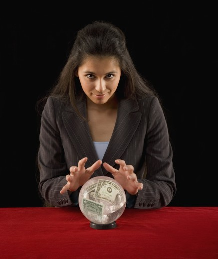 Stock Photo: 1589R-24057 Studio shot of woman with crystal ball with money in it