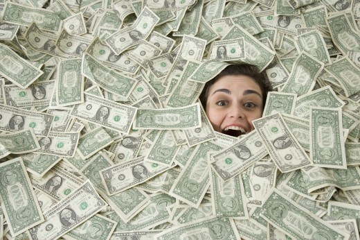 Woman's face peeking out of a pile of money : Stock Photo