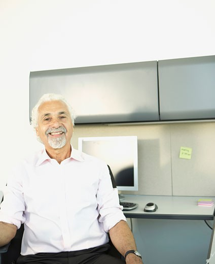 Middle-aged businessman smiling at desk : Stock Photo