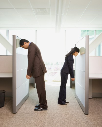 Stock Photo: 1589R-24233 Businessman and businesswoman leaning heads against opposite office cubicle wall