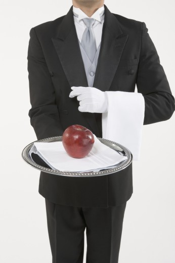 Stock Photo: 1589R-24274 Butler holding a silver tray with an apple